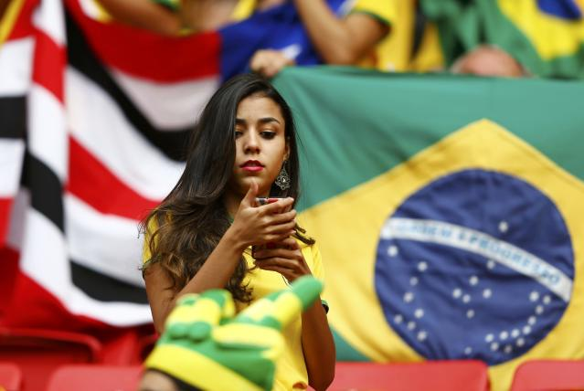 A Brazil fan uses her phone before the 2014 World Cup Group A soccer match between Cameroon and Brazil at the Brasilia national stadium in Brasilia June 23, 2014. REUTERS/Dominic Ebenbichler (BRAZIL - Tags: SOCCER SPORT WORLD CUP)
