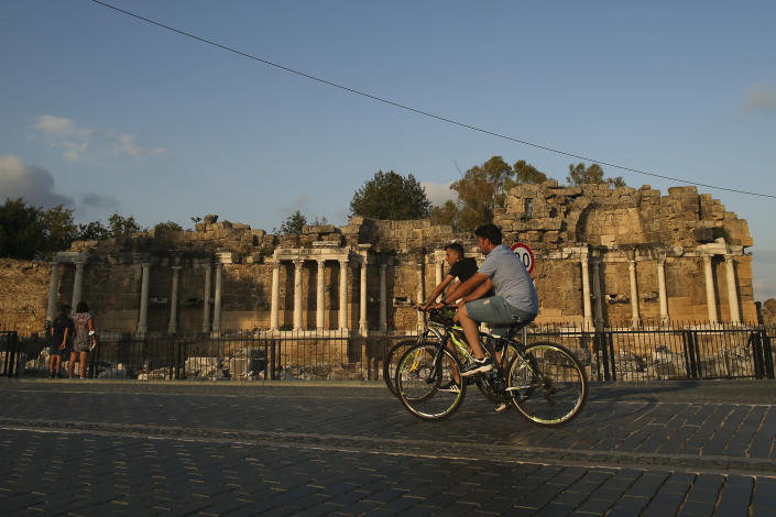 Tourists ride their bicycles in front of an ancient site in Antalya, southern Turkey, on Sunday, June 20, 2021. Hotels in Turkey's Antalya region, a destination beloved by holidaymakers, are preparing to finally resume operations as they expect the return of international tourists after months of setbacks caused by the pandemic that halted travel. (AP Photo/Emrah Gurel)