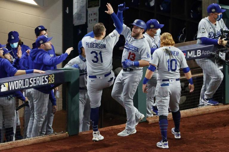 Long ball: Max Muncy is congratulated by teammates Joc Pederson and Justin Turner after a solo home run in the Los Angeles Dodgers game-five victory over Tampa Bay in baseball's World Series