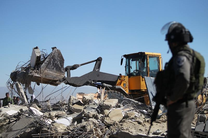 A member of the Israeli security forces stands guard as an Israeli army bulldozer with a demolition permit pulls down the house of a Palestinian family near the West Bank town of Hebron on January 20, 2015 (AFP Photo/Hazem Bader)