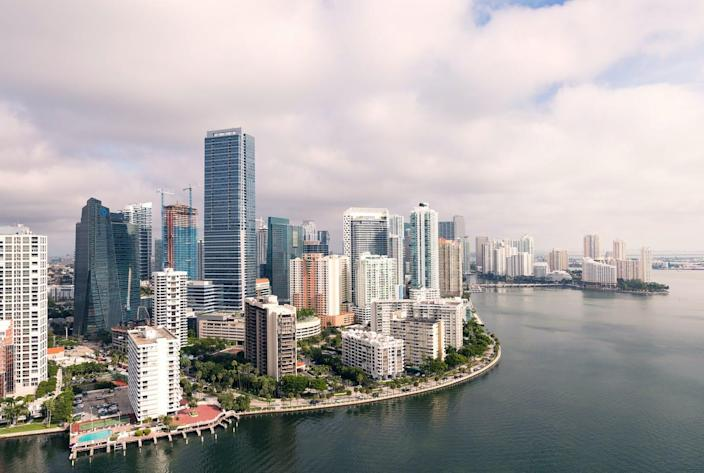 An aerial view of downtown Miami showing waterfront walking paths, parks and pools