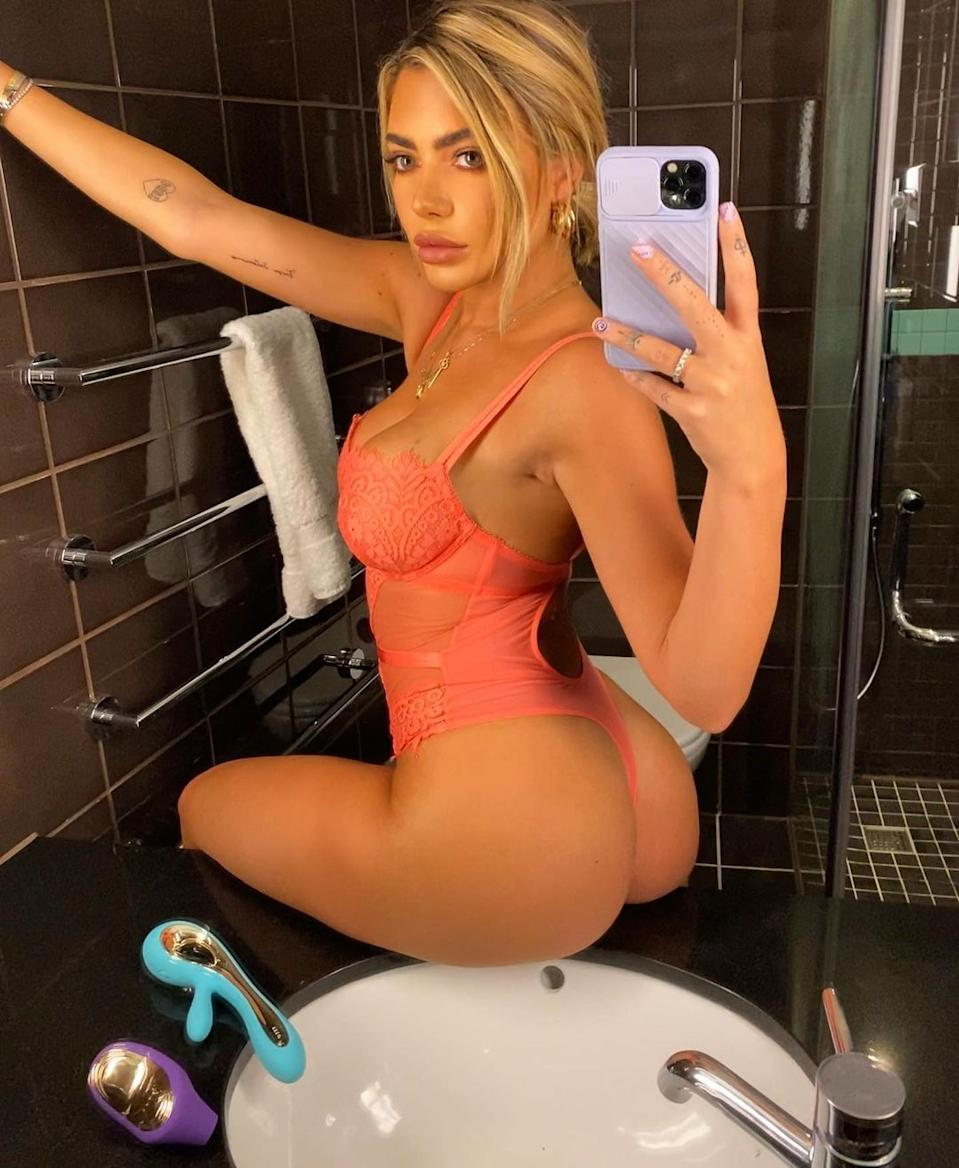 Love Island contestant Megan Barton Hanson poses on a bathroom sink wearing an orange lacy bodysuit