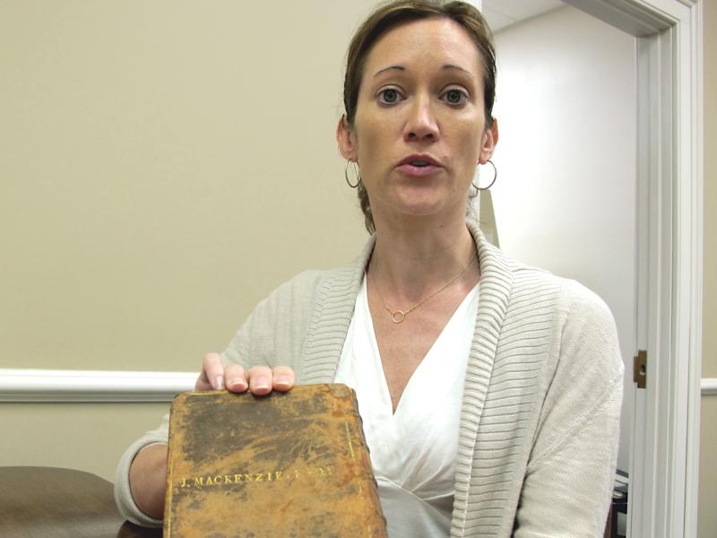 Archivist Trisha Kometer holds up a rare 1743 book at the Charleston Library Society in Charleston, S.C., on Monday, May 7, 2012. The volume, which was found in the vault of the Charleston Library Society, really belongs to the College of Charleston and will be turned over to officials from the college at a ceremony later this week. (AP Photo/Bruce Smith)