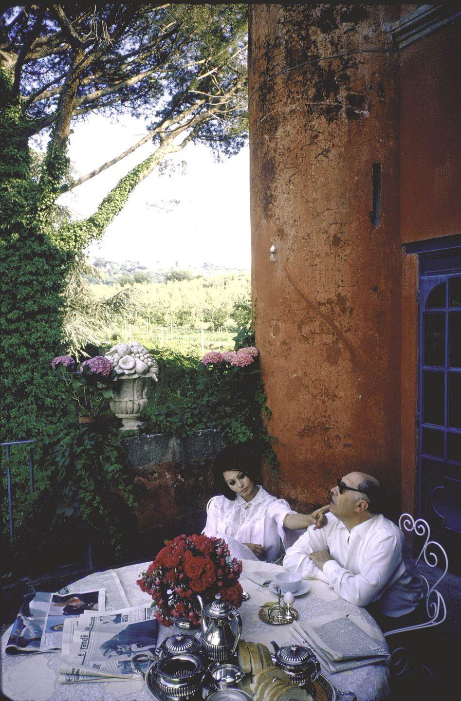 <p>Complete with coffee and the morning newspaper, the Italian film star enjoys a leisurely morning on the terrace of her Roman villa with her director husband, Carlo Ponti. </p>