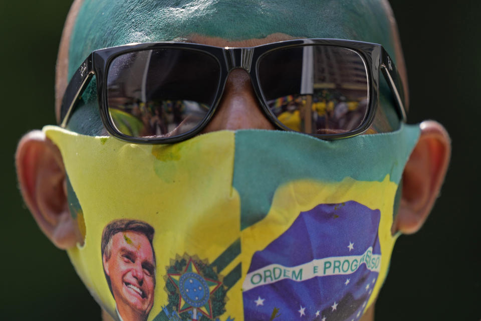 A supporter of Brazilian President Jair Bolsonaro wears a face mask, due to the COVID-19 pandemic, decorated with a photo of Bolsonaro at a rally marking Independence Day in Sao Paulo, Brazil, Tuesday, Sept. 7, 2021. (AP Photo/Andre Penner)