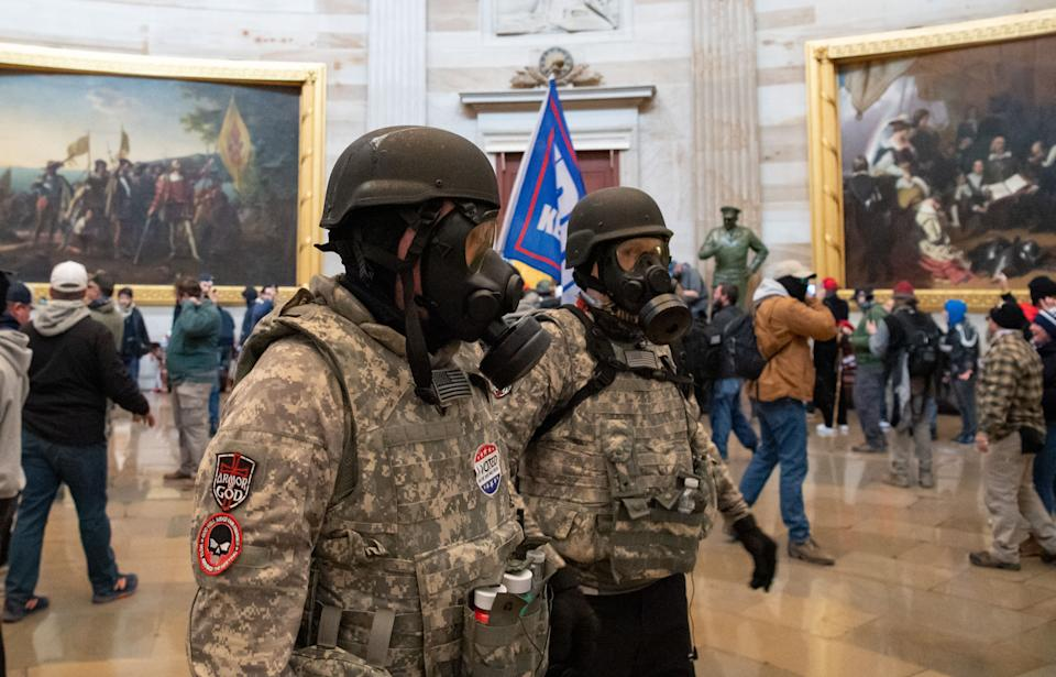 (FILES) Supporters of US President Donald Trump wear gas masks and military-style apparel as they walk around inside the Rotunda after breaching the US Capitol in Washington, DC, January 6, 2021. - Demonstrators breeched security and entered the Capitol as Congress debated the 2020 presidential election Electoral Vote Certification. (Photo by SAUL LOEB / AFP) (Photo by SAUL LOEB/AFP via Getty Images)