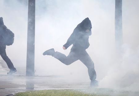 A protester reacts to tear gas canisters fired by police at a demonstration during the Act XXIV (the 24th consecutive national protest on Saturday) of the yellow vests movement in Strasbourg, France, April 27, 2019. REUTERS/Vincent Kessler