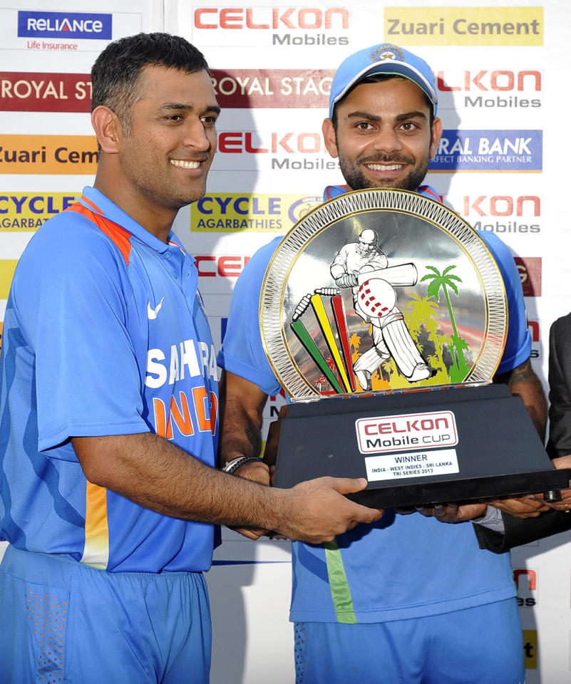 Indian cricket team captain Mahendra Sing Dhoni (L) and teammate Virat Kohli hold their winner trophy at the end of the final match of the Tri-Nation series between India and Sri Lanka at the Queen's Park Oval stadium in Port of Spain on July 11, 2013. India defeated Sri Lanka by 1 wicket to win the series. AFP PHOTO/Jewel Samad