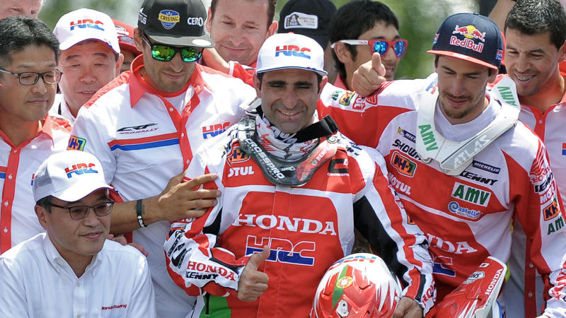 Portuguese rider Paulo Goncalves (C) in 2017 celebrating in the podium after arriving in second place in the 2015 Dakar Rally motorbike category in Buenos Aires. The 40-year-old Goncalves has died after a crash in the Dakar Rally on January 12, 2020, in Saudi Arabia, becoming the gruelling motorsport marathon's 25th fatality. (Photo by ALEJANDRO PAGNI/AFP via Getty Images)