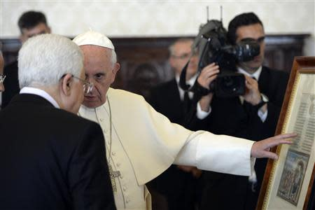 Pope Francis exchanges gifts with Palestinian President Mahmoud Abbas during a private audience in the pontiff library at the Vatican