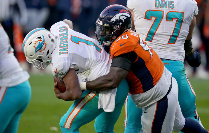 Denver Broncos defensive end DeShawn Williams (90) sacks Miami Dolphins quarterback Tua Tagovailoa (1) during the second half of an NFL football game, Sunday, Nov. 22, 2020, in Denver. (AP Photo/David Zalubowski)