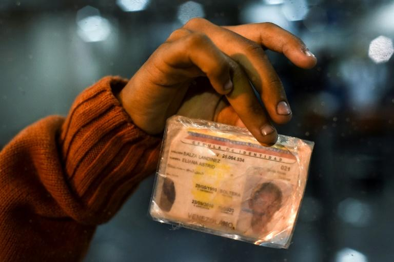 Eliana Balza, 19, shows her damaged Venezuelan identity card, after the Ecuadoran authorities banned her from entering the country
