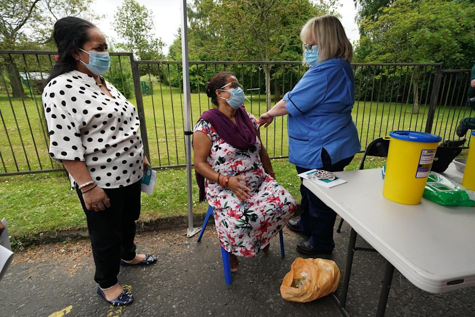 Vaccination nurse Lorraine Mooney gives a vaccination to members of the public outside a bus in the car park of Crieff community hospital in Perth and Kinross (Andrew Milligan/PA) (PA Wire)