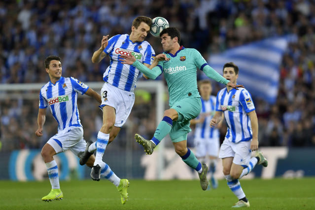 Barcelona's Carles Alena, center right, jumps for the ball with Real Sociedad's Diego Llorente during the Spanish La Liga soccer match between Real Sociedad and Barcelona, at Anoeta stadium, in San Sebastian, Spain, Saturday, Dec. 14, 2019. (AP Photo/Alvaro Barrientos)