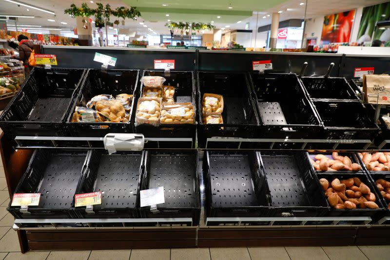 FILE PHOTO: Partially emptied shelves are pictured at a Rewe grocery store in Potsdam