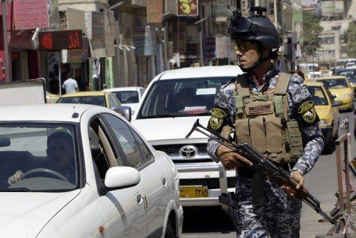 An Iraqi police officer guards a checkpoint in central Baghdad on August 4, 2012