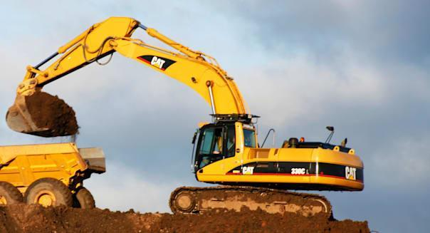 caterpillar 330c tracked excavator and bell b25d articulated dump truck at work on a building site excavating soil