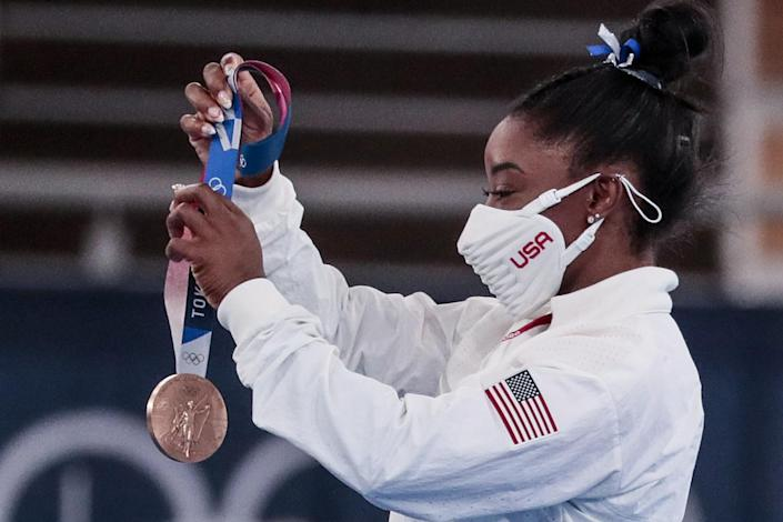 Simone Biles holds the bronze medal she won in the balance beam final.