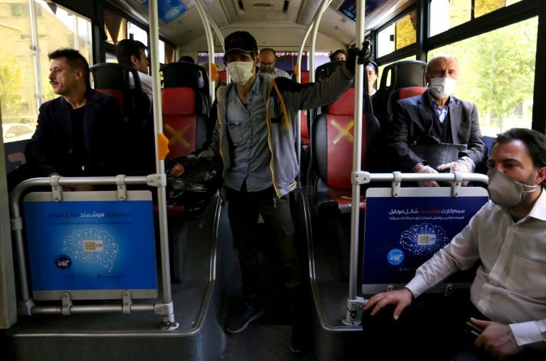 Iranian men keep their distance from one another to prevent the spread of COVID-19 while traveling by bus in Tehran (AFP Photo/ATTA KENARE)
