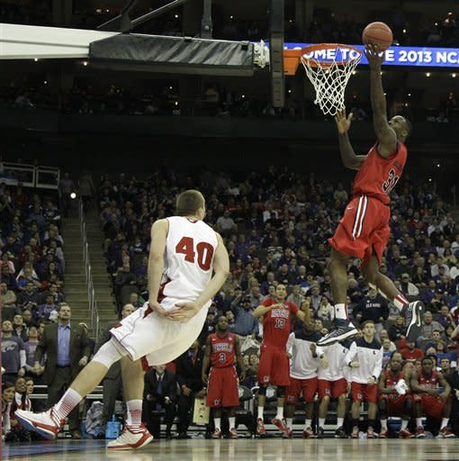 Mississippi forward Murphy Holloway (31) gets past Wisconsin forward/center Jared Berggren (40) to score during the second half of a second-round game of the NCAA college basketball tournament Friday, March 22, 2013, in Kansas City, Mo. Mississippi won 57-46. (AP Photo/Charlie Riedel)