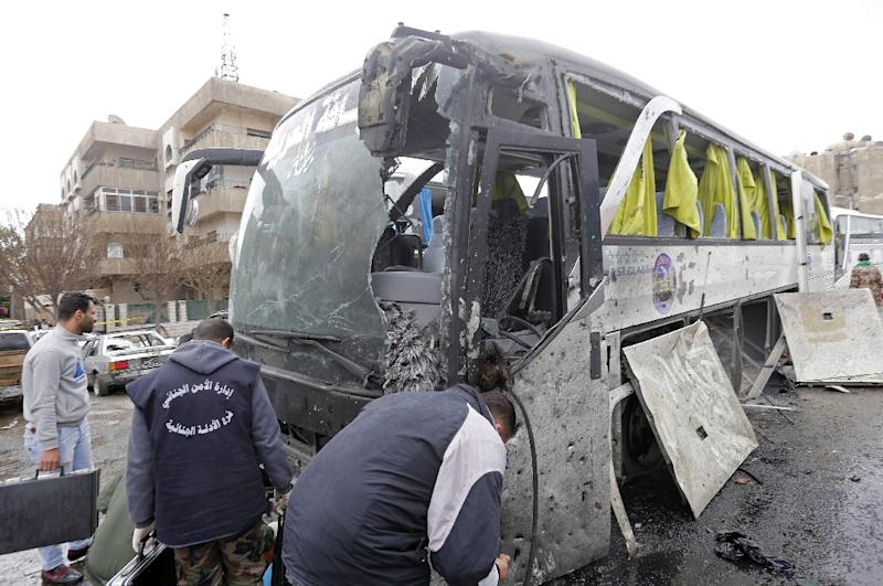 Syrian forensics experts examine a damaged bus following bomb attacks in Damascus' Old City on March 11, 2017