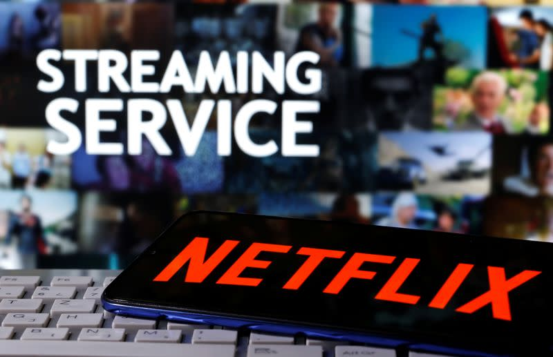 """A smartphone with the Netflix logo is seen on a keyboard in front of displayed """"Streaming service"""" words in this illustration"""