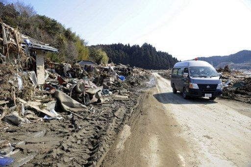 A police van moves carefully along a road past damaged homes and amongst piles of debris left by the tsunami in 2011
