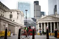 FILE PHOTO: The Bank of England can be seen as people cycle through the City of London financial district
