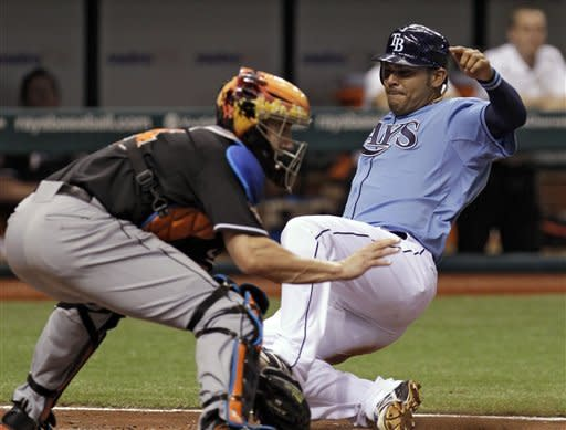 Tampa Bay Rays' Carlos Pena, right, slides safely into home plate ahead of the throw to Miami Marlins catcher John Buck, left, during the fifth inning of an interleague baseball game on Friday, June 15, 2012, in St. Petersburg, Fla. Pena scored on a single by teammate Will Rhymes. (AP Photo/Chris O'Meara)