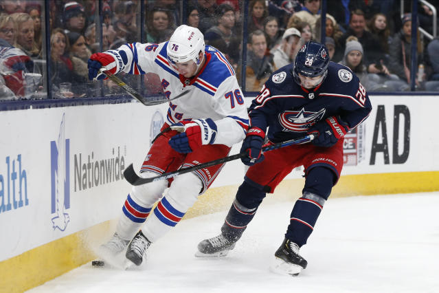 New York Rangers' Brady Skjei, left, tries to clear the puck as Columbus Blue Jackets' Oliver Bjorkstrand, of Denmark, defends during the second period of an NHL hockey game Friday, Feb. 14, 2020, in Columbus, Ohio. (AP Photo/Jay LaPrete)