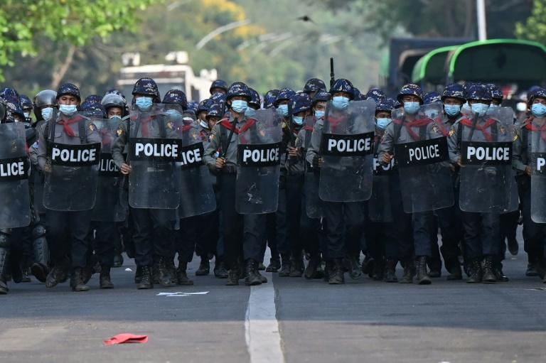 Police march on a road to clear away protesters from holding a demonstration against the military coup in Yangon