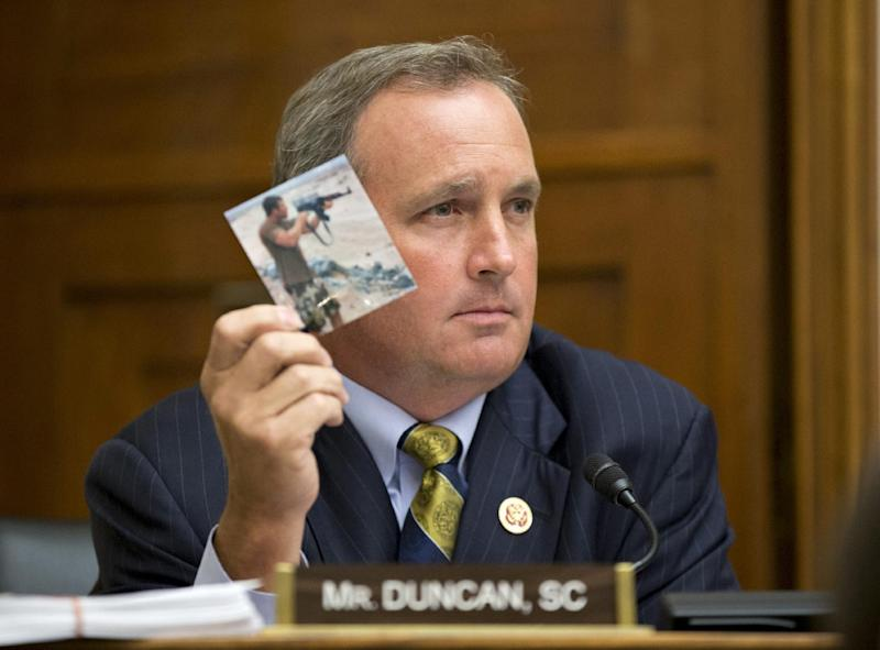 While confronting Secretary of State John Kerry at a House Foreign Affairs Committee hearing on Syria, Rep. Jeff Duncan, R-S.C., holds up a photo of Navy SEAL Tyrone Woods who died in Benghazi, Libya, Wednesday, Sept. 4, 2013, on Capitol Hill in Washington. Woods was one of four Americans slain in an attack on a U.S. compound in Libya last year. (AP Photo/J. Scott Applewhite)