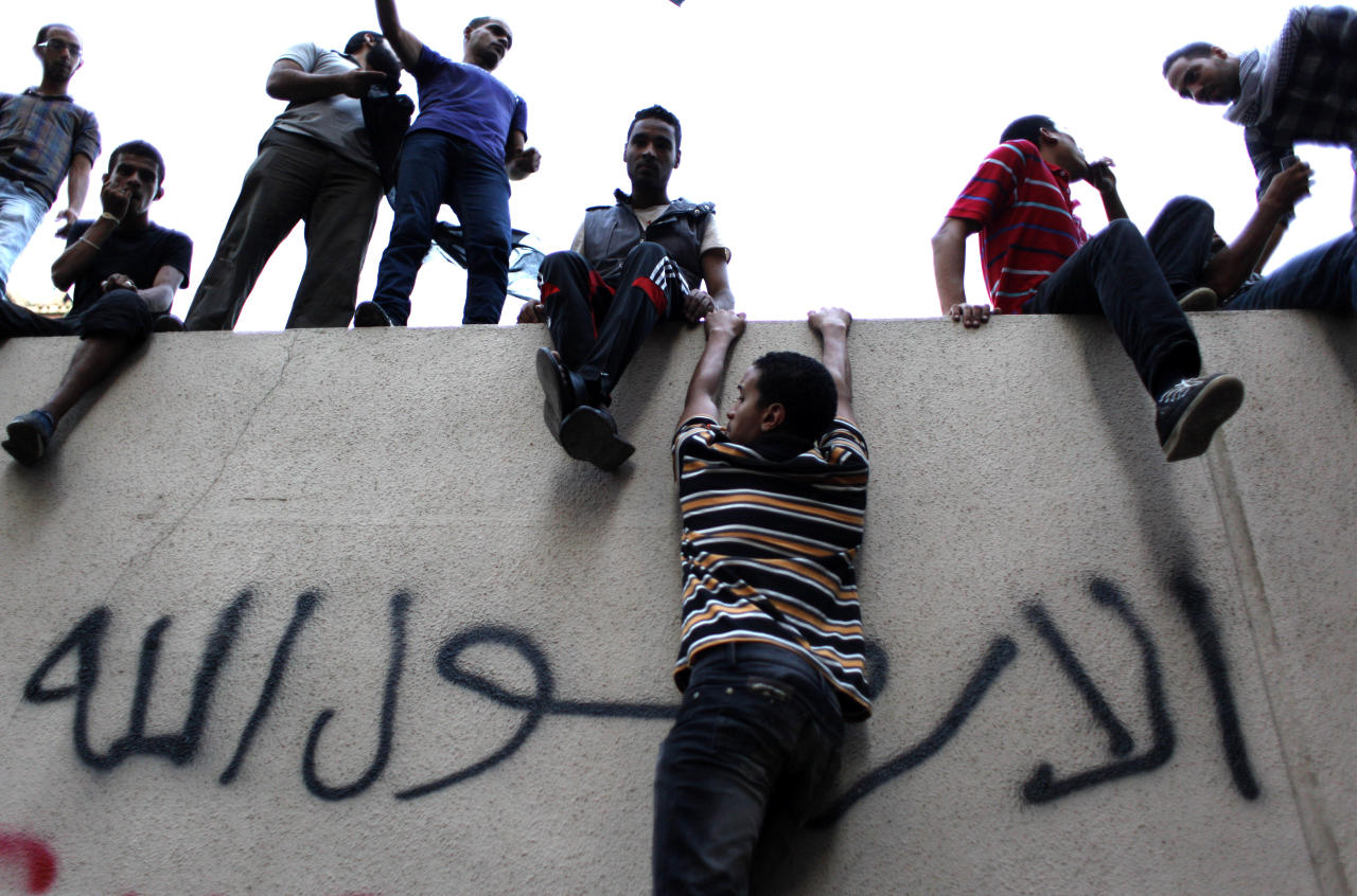"Egyptian protesters climb the walls of the U.S. embassy with Arabic graffiti that reads ""any one but you God's prophet"" during a protest in Cairo, Egypt, Tuesday, Sept. 11, 2012. Egyptian protesters, largely ultra conservative Islamists, have climbed the walls of the U.S. embassy in Cairo, went into the courtyard and brought down the flag, replacing it with a black flag with Islamic inscription, in protest of a film deemed offensive of Islam. (AP Photo/Nasser Nasser)"