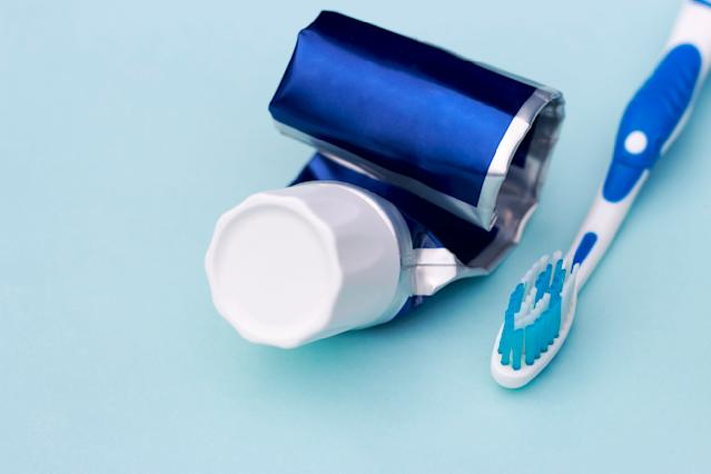 Empty tube of toothpaste and toothbrush on blue background