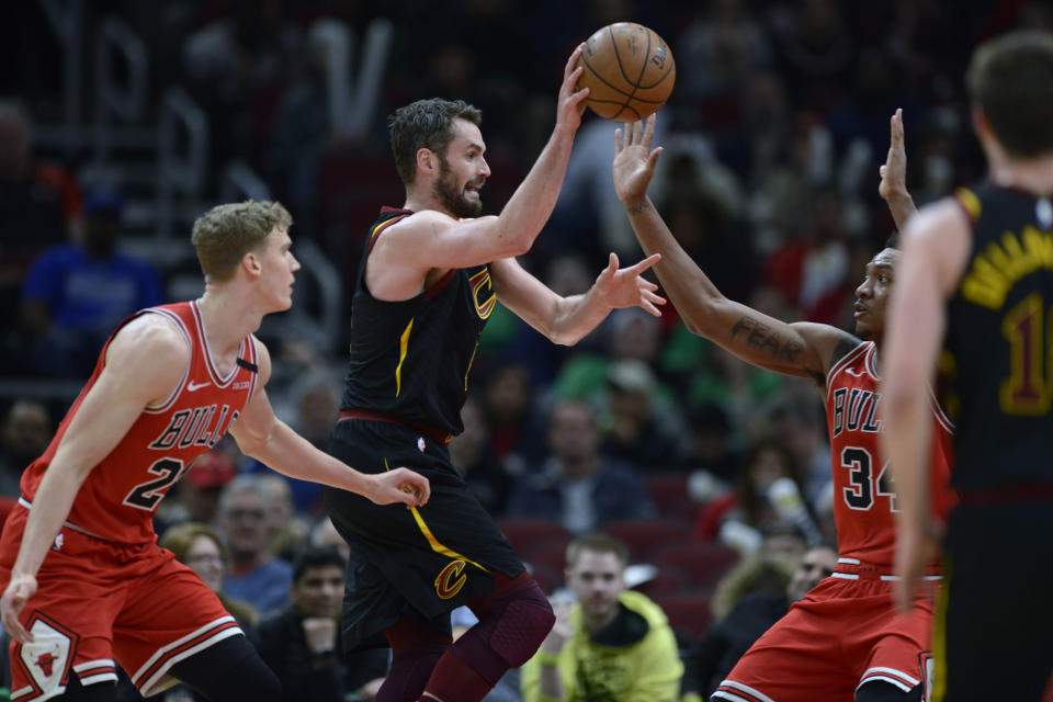 Cleveland Cavaliers' Kevin Love (0) passes the ball asChicago Bulls' Wendell Carter Jr. (34) and Lauri Markkanen (24) defend during the second half of an NBA basketball game Tuesday, March 10, 2020, in Chicago. (AP Photo/Paul Beaty)