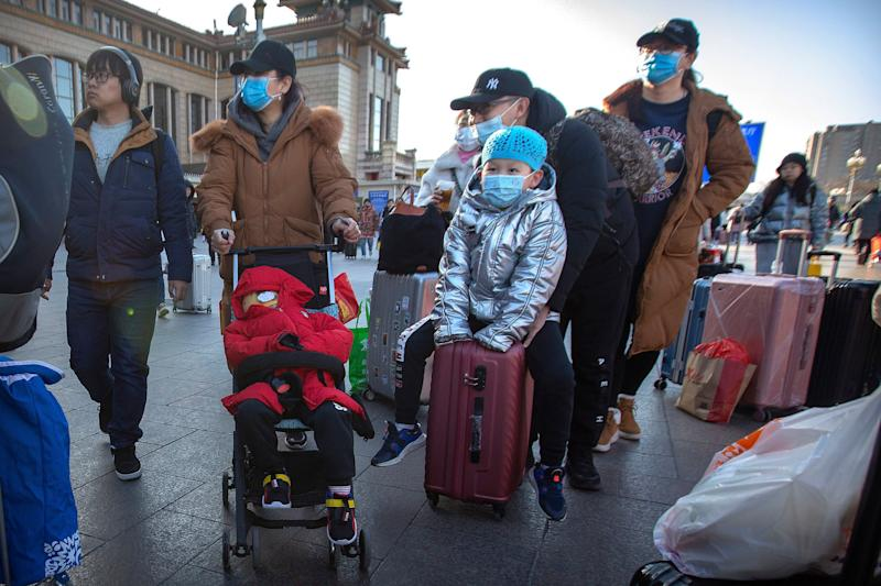Travelers wear face masks outside of the Beijing Railway Station on Jan. 20, 2020. China reported a sharp rise in the number of people infected with a new coronavirus on Monday, including the first cases in the capital. The outbreak coincides with the country's busiest travel period as millions board trains and planes for the Lunar New Year holidays.  (Photo: ASSOCIATED PRESS)