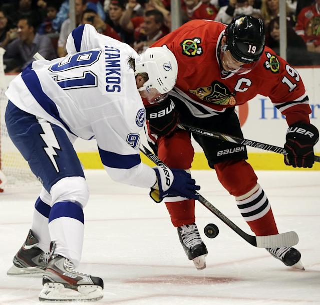 Tampa Bay Lightning's Steven Stamkos (91) vies for the puck against Chicago Blackhawks' Jonathan Toews (19) during the first period of an NHL hockey game in Chicago, Saturday, Oct. 5, 2013. (AP Photo/Nam Y. Huh)