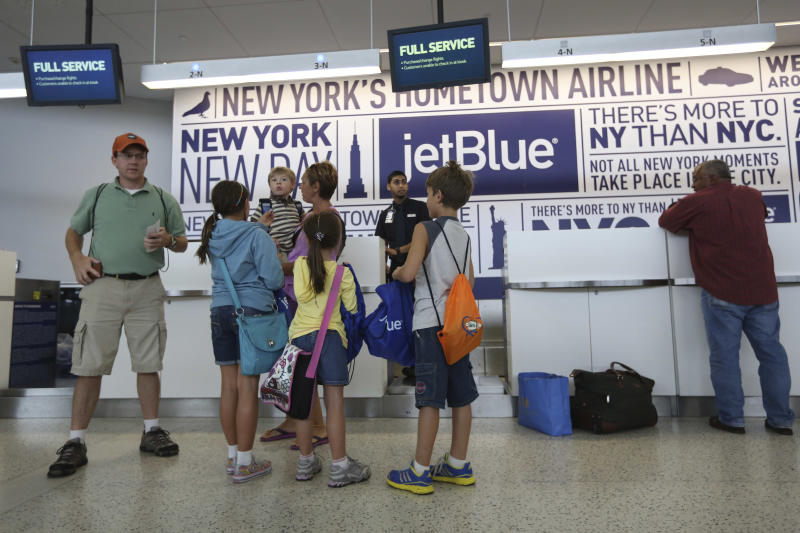 Tom Price, left, and his wife Zsuzsa, center, prepare to check in with their children, from left, Hailye, 10, Callum, 4, Keira, 6, and Owen, 9, at the JetBlue counter, Saturday, Sept. 21, 2013 at JFK airport in New York. Dozens of families with children with autism have practiced air travel at New York's Kennedy International Airport. JetBlue Airways and the nonprofit Autism Speaks held the practice run for families at JFK on Saturday. (AP Photo/Mary Altaffer)