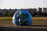 A woman jumps on an inflatable globe outside the stadium in Kaliningrad, Russia, June 28, 2018. REUTERS/Kacper Pempel