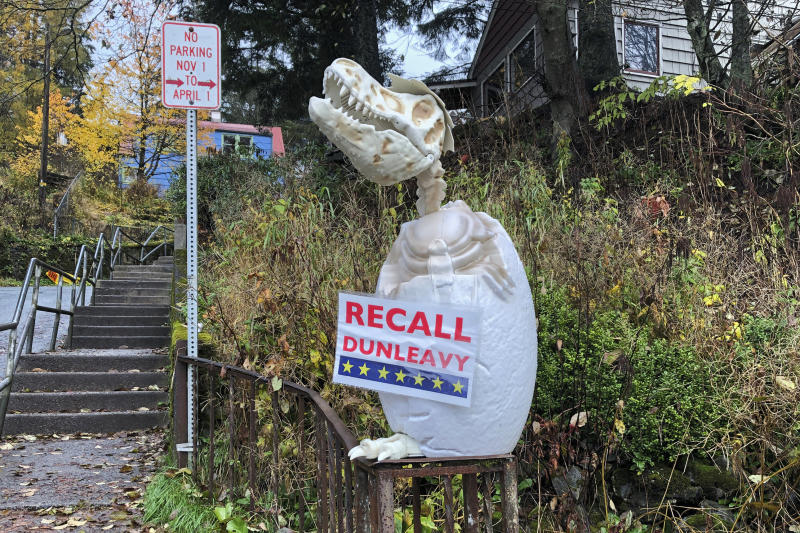 """In this Friday, Nov. 1, 2019, photo, a sign reading """"Recall Dunleavy"""" hangs from a decoration in front of a yard near the Alaska governor's mansion in Juneau, Alaska. A fight is brewing in the state over whether Republican Gov. Mike Dunleavy should be recalled from office, with his critics saying he's incompetent and has recklessly tried to cut spending while supporters see a politically motivated attempt to undo the last election. (AP Photo/Becky Bohrer)"""