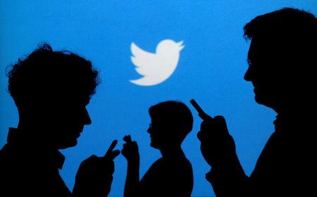 FILE PHOTO: People holding mobile phones are silhouetted against a backdrop projected with the Twitter logo in this illustration picture taken in Warsaw, Poland, September 27, 2013.   REUTERS/Kacper Pempel/File Photo