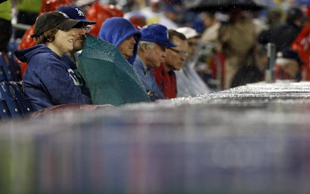 Fans sit in the rain during the second inning of a baseball game between the Los Angeles Dodgers and the Washington Nationals at Nationals Park, Monday, May 5, 2014, in Washington. (AP Photo/Alex Brandon)