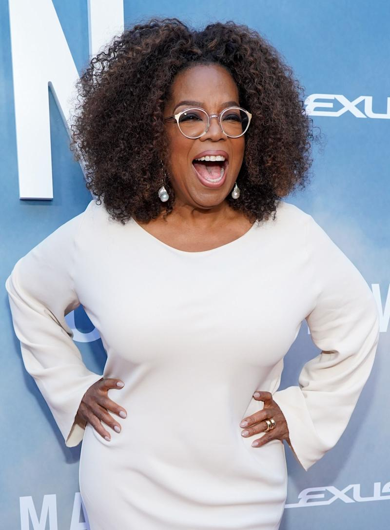 Oprah Winfrey stuns in white long-sleeve dress as she poses for the camera with her hands on her lips and a wide smile on her face.