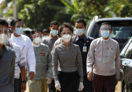 Myanmar leader Aung San Suu Kyi, center, wearing a protective face mask and shield walks to greet supporters as she leaves after a demonstration of the voting for the upcoming Nov. 8 general elections, Tuesday, Oct. 20, 2020, in Naypyitaw, Myanmar. (AP Photo/Aung Shine Oo)