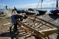 A boat-builder constructs the frame of a new boat in Cap-Haitien, Haiti