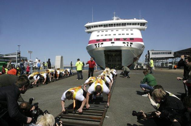 "Estonia's strong man team pulls ""Baltic Queen"", a 21746 ton passenger ferry, in Tallinn May 20, 2011. The athletes set a new world record for the heaviest weight pulled by manpower, organizers said. REUTERS/Ints Kalnins"