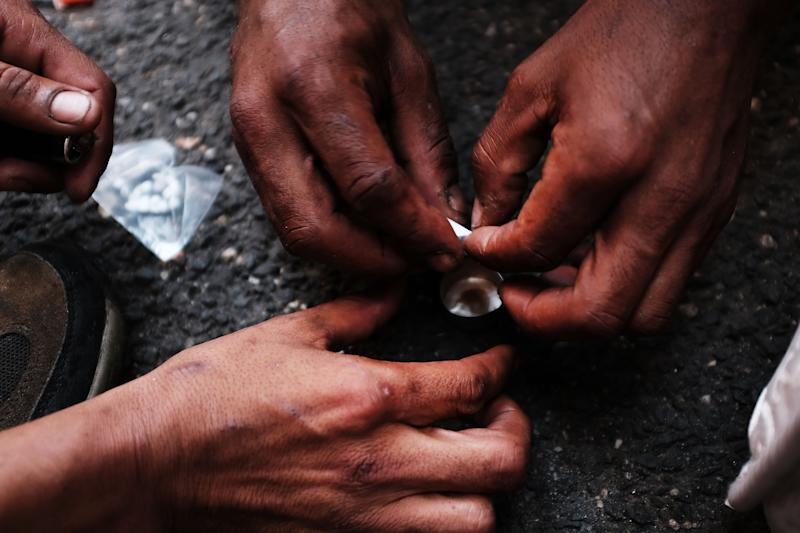 Heroin users prepare to shoot up on the street in a South Bronx neighborhood