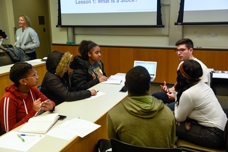 High school students gathered around a table discuss stock investing.