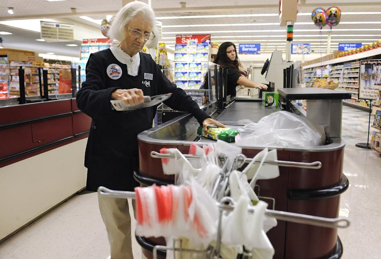 In this Sept. 23, 2011 photo, cashier Joyce Mackie bags groceries as a customer uses a self-serve checkout station at a Big Y supermarket in Manchester, Conn. A growing number of supermarket chains are bagging their self-serve checkout lanes, saying they can offer better customer service when clerks help shoppers directly. Big Y Foods, which has more than 60 southern New England locations, recently became the latest to announce it's phasing them out. (AP Photo/Jessica Hill)