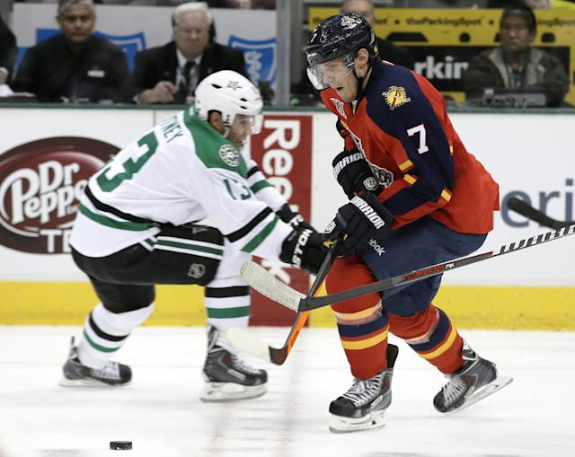 Dallas Stars' Ray Whitney (13) defends as Florida Panthers' Dmitry Kulikov (7), of Russia, moves the puck upice in the first period of a preseason NHL hockey game on Wednesday, Sept. 18, 2013, in Dallas. (AP Photo/tony gutierrez)